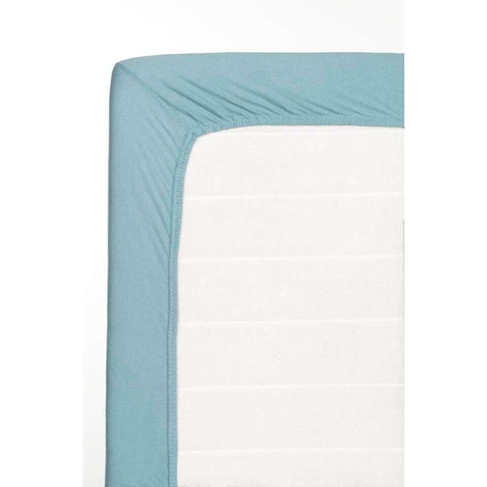 Dit zachte hoeslaken is gemaakt van jersey katoen en steenblauw van kleur. Dit hoeslaken heeft een afmeting van 180x200 cm.